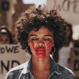 Woman standing outdoors with imprint of a bloody hand on her mouth during demonstration. Protesting to stop women abuse.